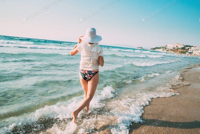 Young Caucasian Lady Woman In Summer Hat Runs Along The Seashore Sea Beach. Vacation On Sea Ocean