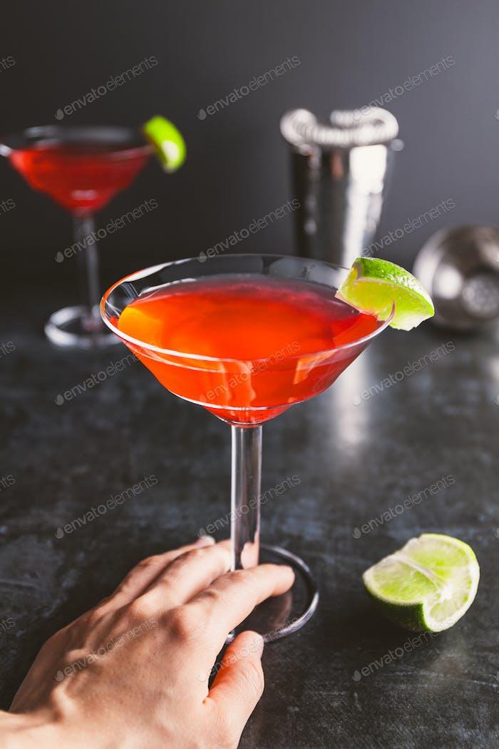 Roter Cocktail mit Limette in Martini-Glas auf einem Tisch.