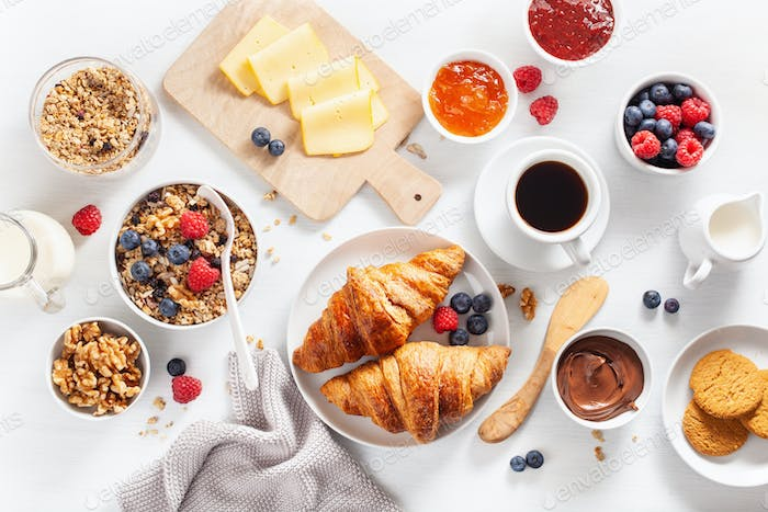 healthy breakfast with granola, berry, nuts, croissant, jam, cho