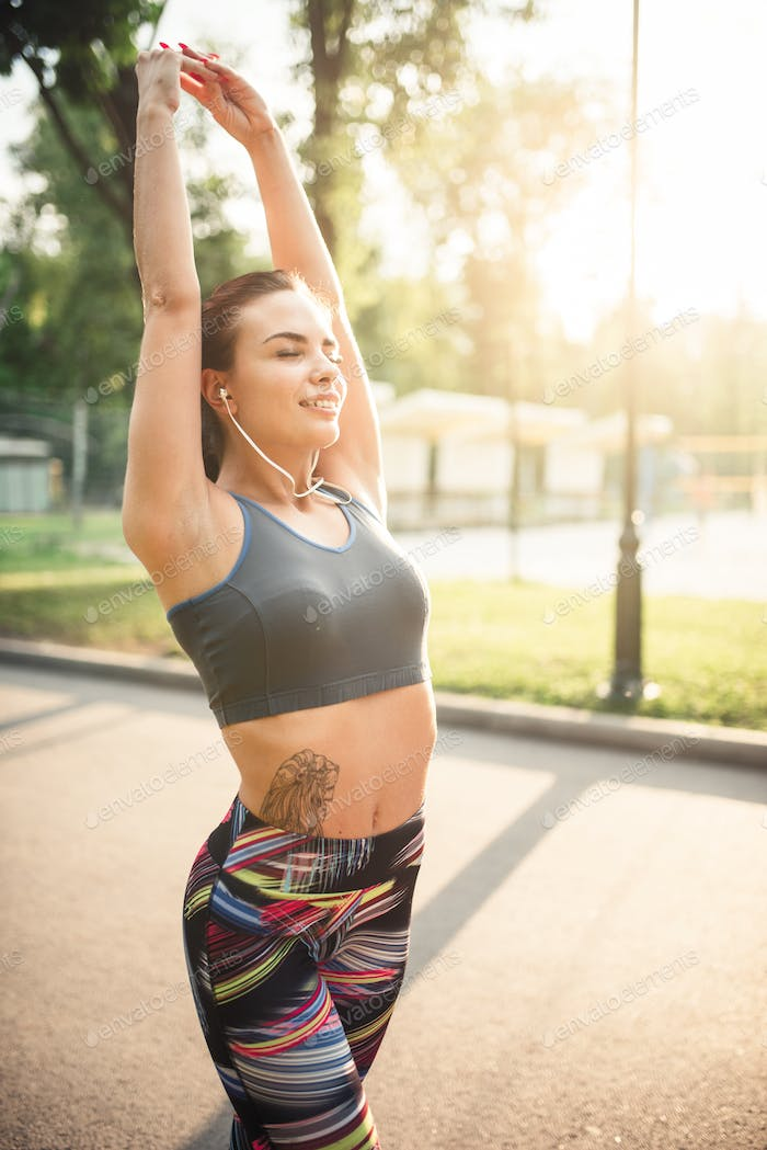 Athletic girl on morning fitness training in park