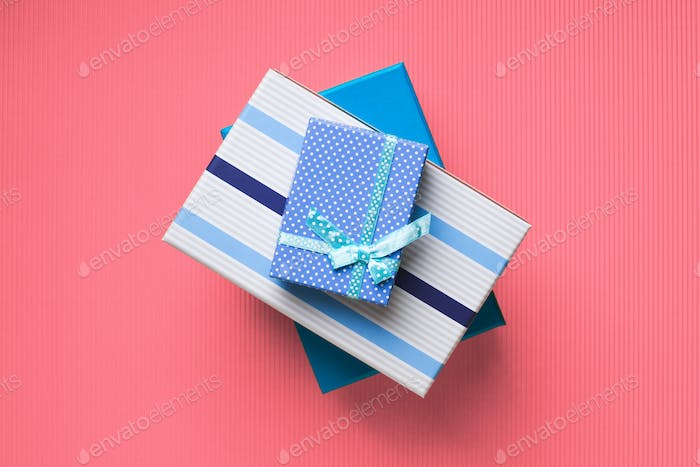 Gift boxes stack on pink coral background