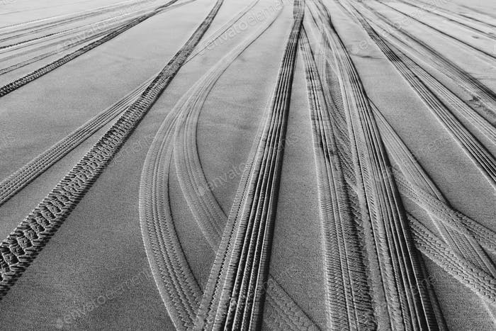 Tire tracks on the soft surface of sand on a beach.