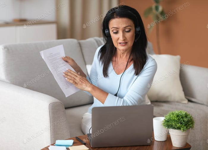 Woman in headset sitting at desk, having videocall on laptop