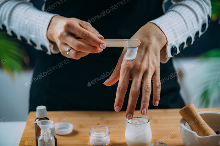 Woman Applying Homemade Hand Cream onto her Hands