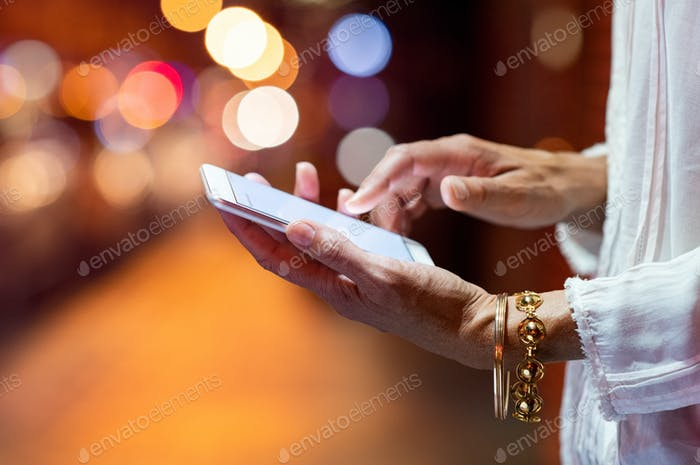 Woman hands using smartphone at night