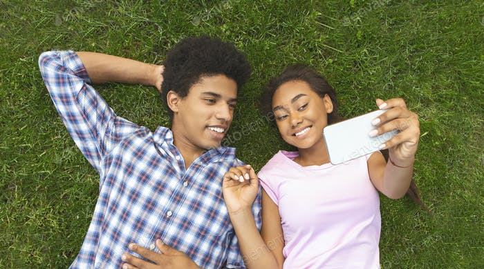 Teenage couple making selfie while laying on grass