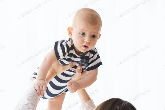 Closeup portrait of lovely baby lifted in air by mother