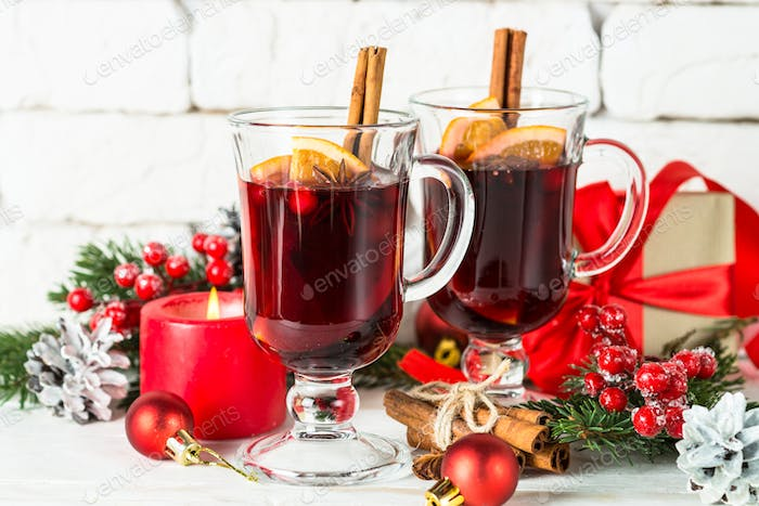 Mulled wine in glass mug with fruit and spices on white