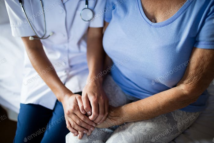 Female doctor consoling senior woman in the bedroom