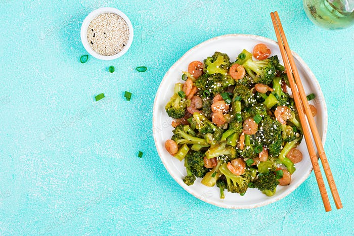 Stir fry shrimp with broccoli close up on a plate. Prawns and broccoli.  Top view, overhead