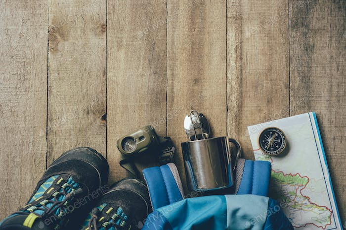 Children's set of equipment for hiking in the mountains on a wooden background