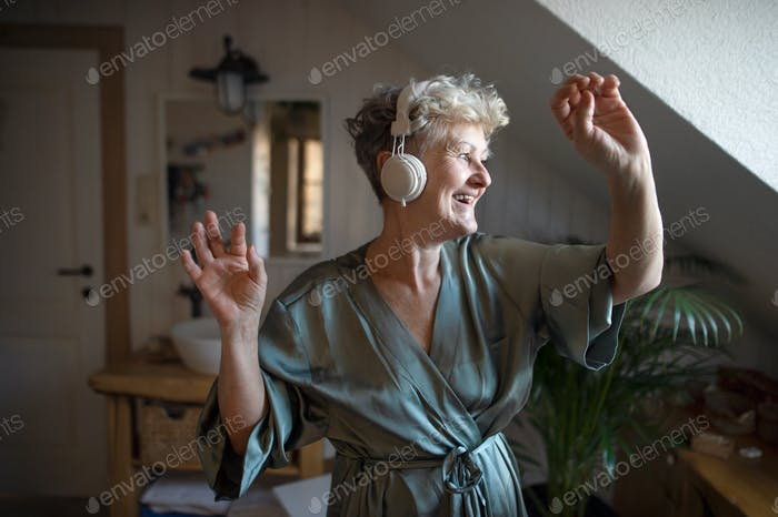 Happy senior woman with headphones dancing at home, relax and self-care concept