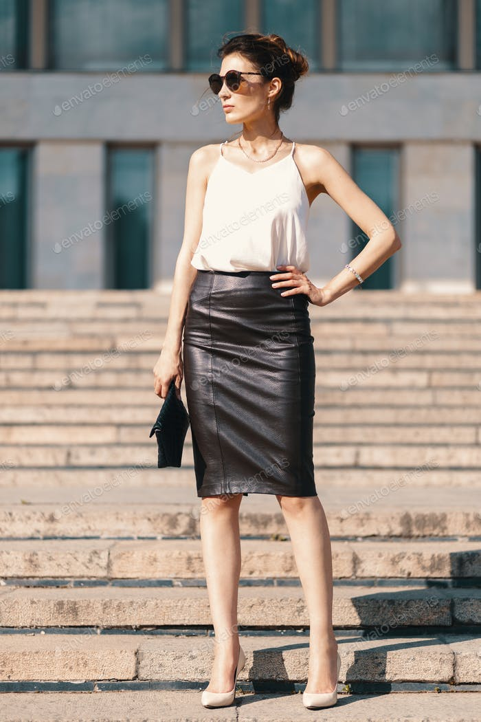 Fashionable brunette businesswoman in leather pencil skirt and s