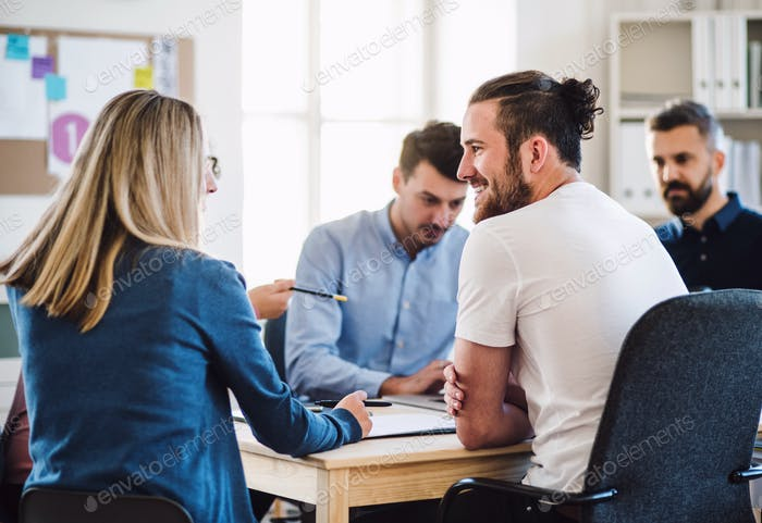 Group of young businesspeople sitting around table in a modern office, having meeting.