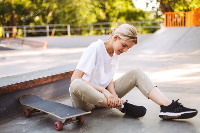 Young skater girl holding her painful leg with skateboard near a