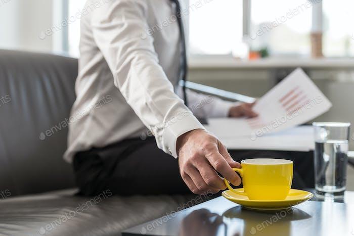 Geschäftsmann sitzt auf seiner Bürocouch und greift nach seiner gelben Kaffeetasse