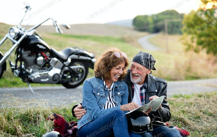 Cheerful senior couple travellers with map and motorbike in countryside.