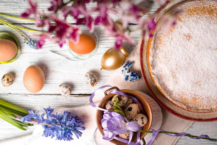 Easter decoration  , flowers and German Easter cake on the white wooden table top view