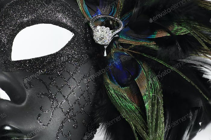Diamond wedding ring on feathers and mask
