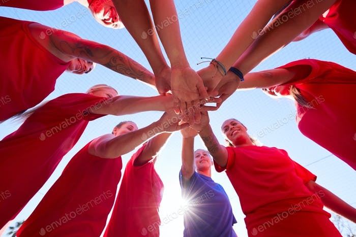 Low Angle View Of Manager Joining Hands With Womens Soccer Team During Pep Talk Before Match