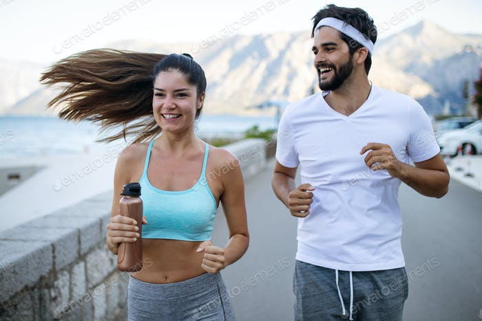 Happy young fit people couple running outdoor