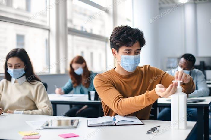 Asiatischer Student, der antibakterielles Desinfektionsmittel