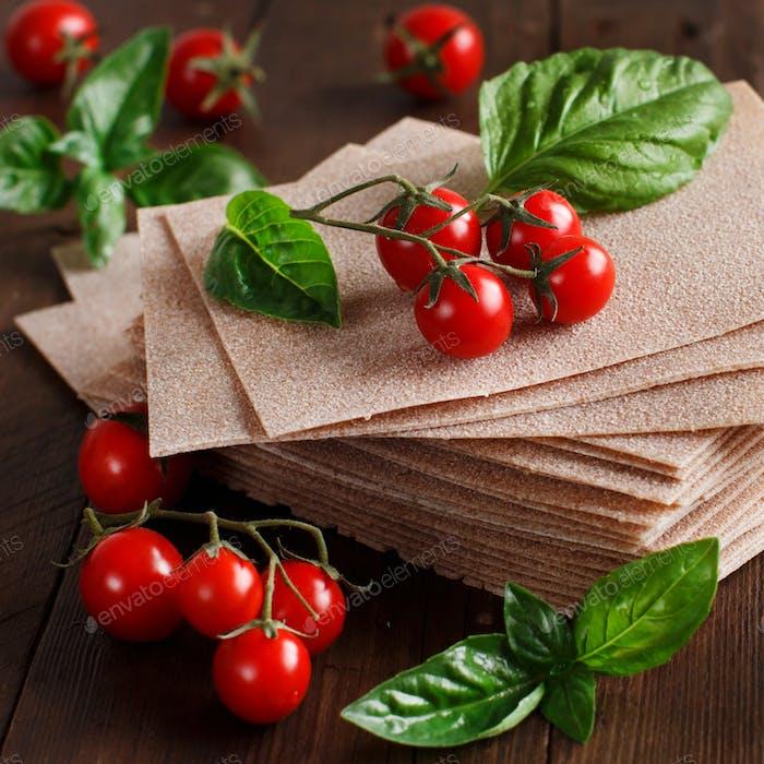 Raw lasagna sheets and cherry tomatoes