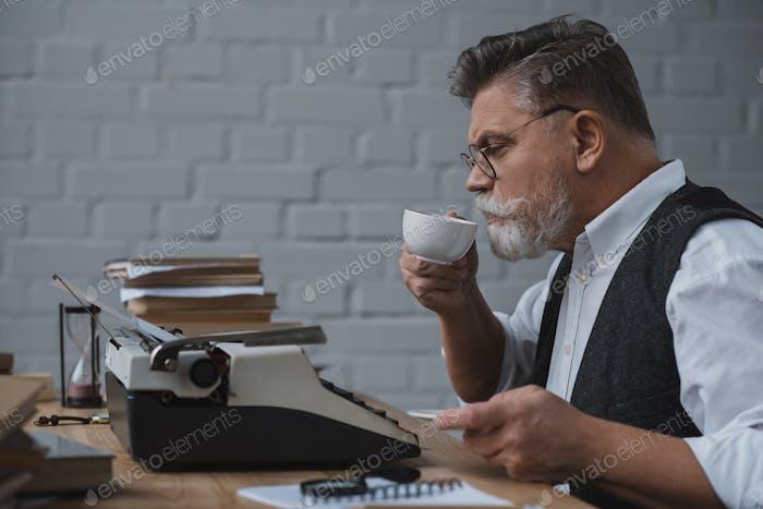 Senior Writer arbeitet mit Vintage-Schreibmaschine und trinkt Kaffee