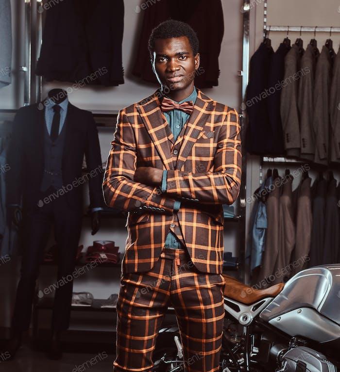 Афро-американский мужчина, одетый в модный элегантный костюм позирует в магазине мужской одежды