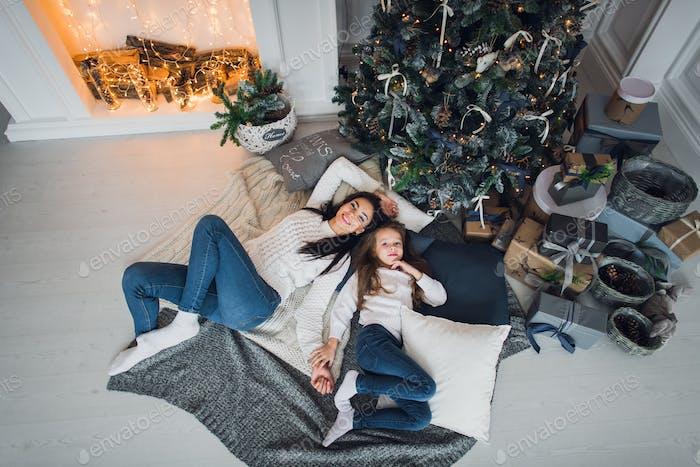 Für immer beste Freunde. Top-Ansicht der glücklichen Mama und ihre Tochter tragen Jeans und weiße Pullover liegen