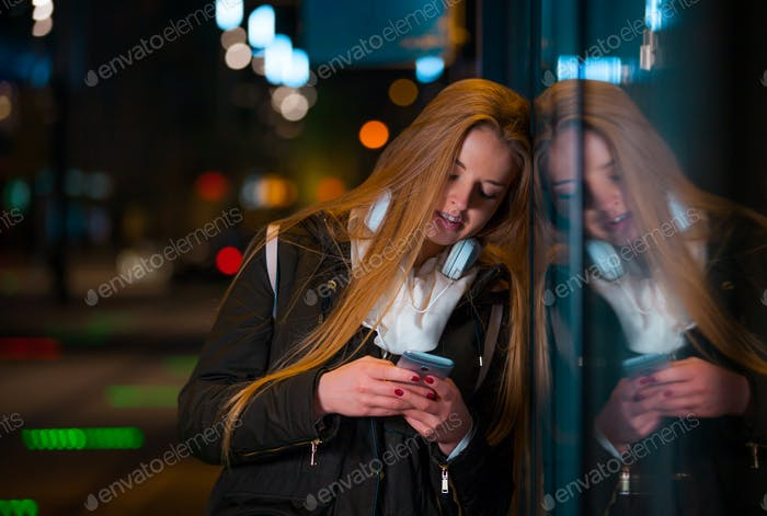 Woman with headphones using tablet waiting on bus stop at night in city