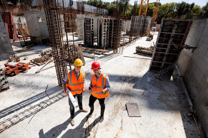 Civil engineer and architect dressed in orange work vests and hard bats discuss the construction