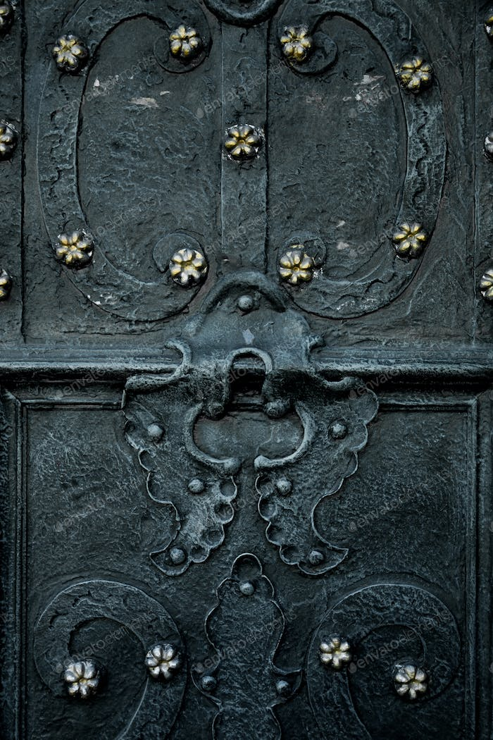Vintage black door decorated with metal flower. Close up.