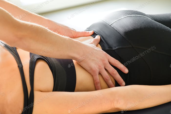 Osteopath doing sacral decompression osteopathy