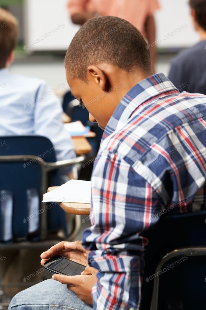 Männliche Schüler senden Textnachricht in Klassenzimmer