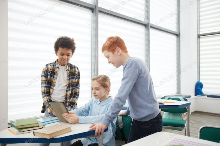 Kinder, die Tablet im Schulunterricht verwenden