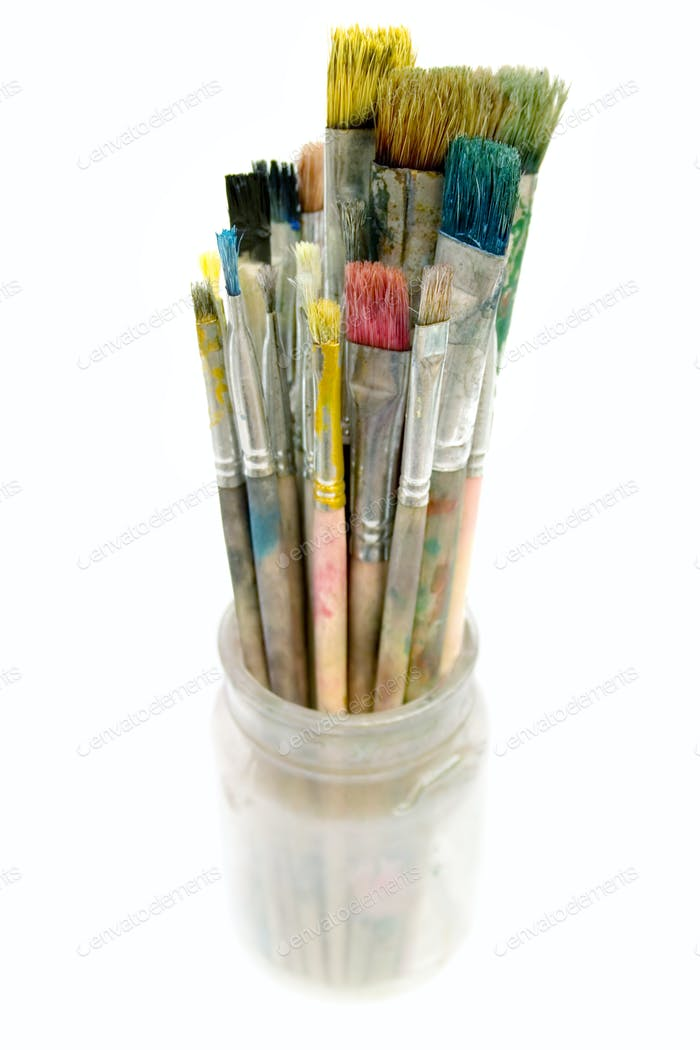 Used Paintbrushes in a Glass Isolated on a White Background