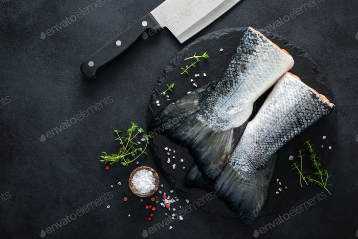Raw salmon fishtails with ingredients for cooking on black background, top view
