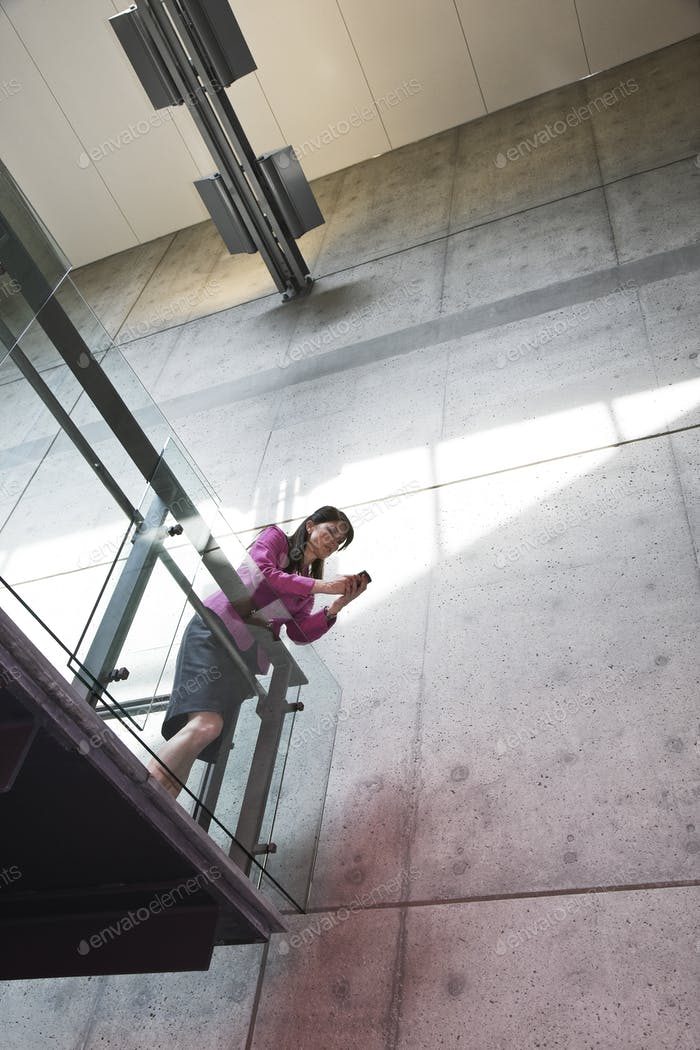 Businesswoman texting from a stairway balcony in large office buidling.