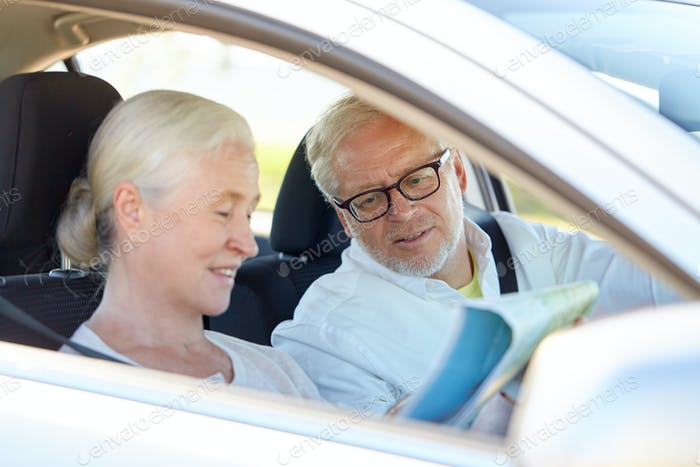 happy senior couple with map driving in car