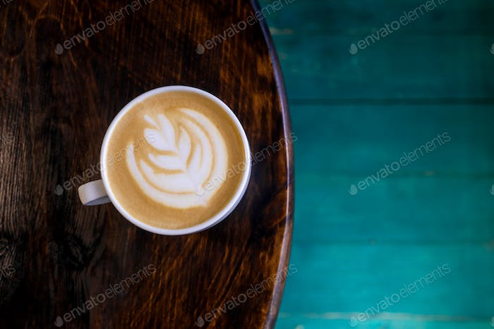 Cup of latte with art on table.