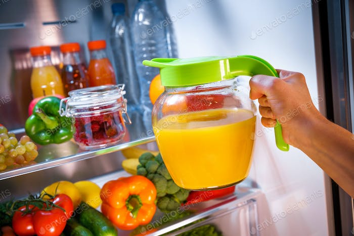 Woman takes the Orange juice from the open refrigerator