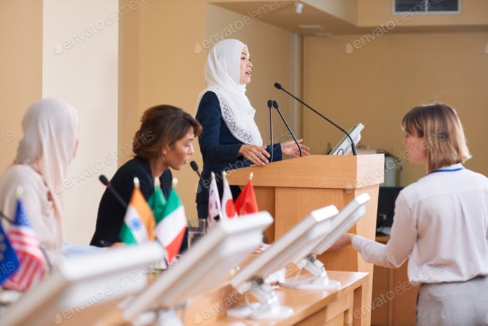 Young contemporary female delegate in hijab and suit