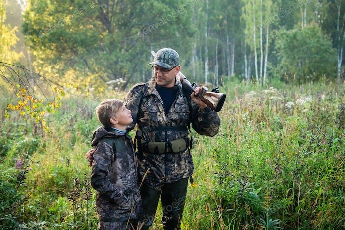 Ein kleiner Junge auf der Jagd mit einem erfahrenen Lehrer im Wald.