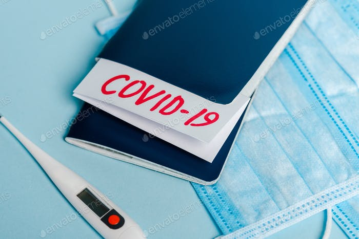 medical masks, thermometer and passports with covid-19 lettering on blue background