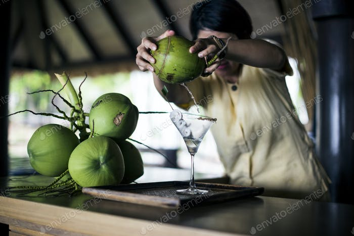 A bartender mixing a martini (Praow-Tini) out of a coconut shaker.
