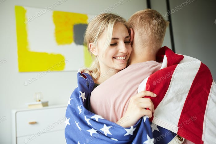 Young embracing couple wrapped into American national flag