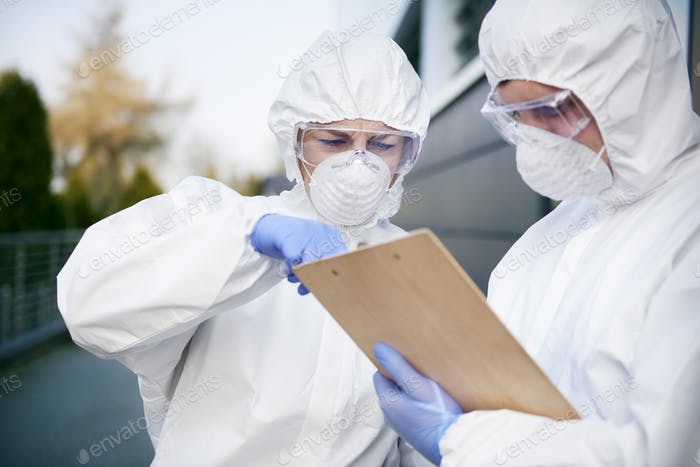 Two technicians with document wearing a protective suit