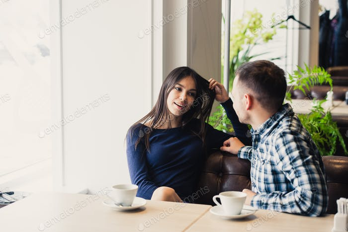 Happy couple talking at cafe, drinking tea