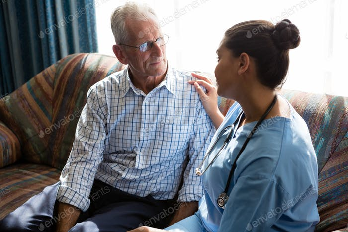 Female doctor consoling senior man on sofa in nursing home